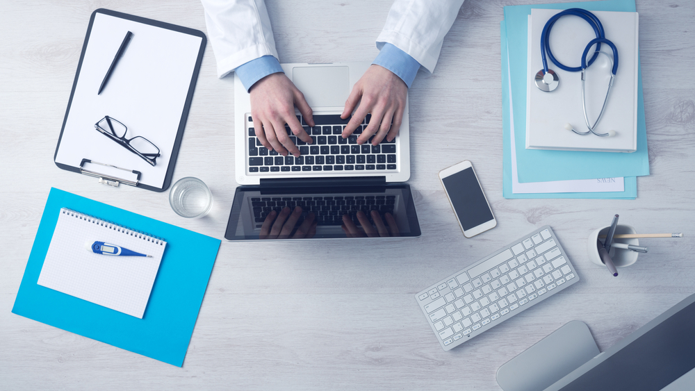 Doctor,Sitting,At,Office,Desk,And,Working,On,His,Laptop